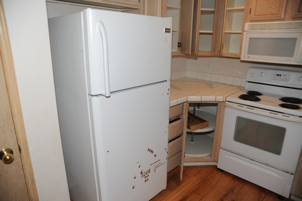 Refrigerator missing a handle and other damage.